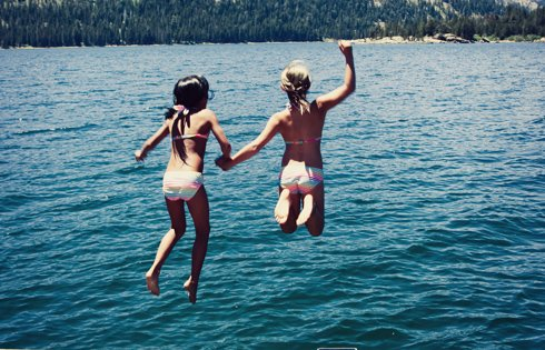 Friends holding hands and jumping into Silver Lake