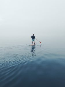 Man paddle boarding on foggy lake